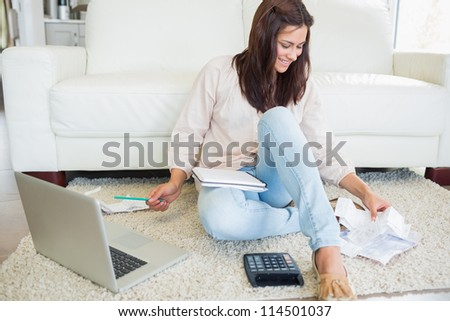 Woman using laptop to calculate bills on floor of living room - stock photo
