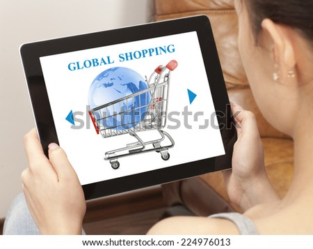 Woman using laptop with online global shopping cart on screen - stock photo