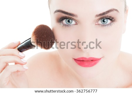 Woman using make-up brush on face cheeks and wearing cosmetics - stock photo