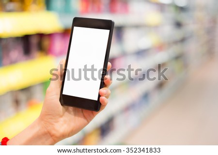 Woman using mobile phone in grocery store  - stock photo