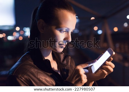 Woman using mobile phone in the city, night light background - stock photo