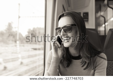 Woman using mobile phone on the train - stock photo