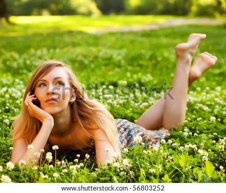 Woman using mobile phone outdoors - stock photo