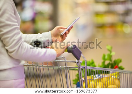 Woman using mobile phone while shopping in supermarket, trolley  - stock photo