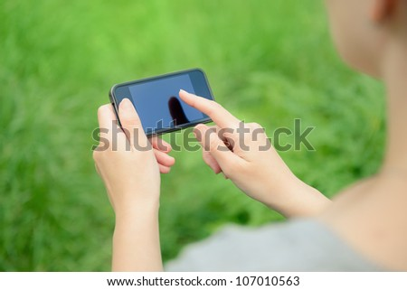Woman using mobile smart phone in the park. - stock photo