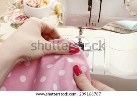 Woman using sewing machine - stock photo