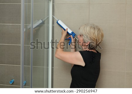 Woman using silicone cartridge for fixing aluminum batten of shower cabin - stock photo