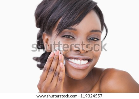 Woman using skin cream on her face - stock photo