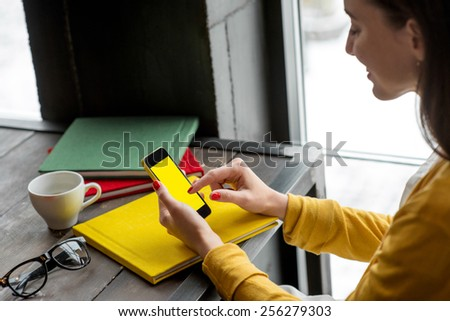 Woman using smart phone on the table with colorful books in the cafe near the window. Phone with empty screen for your application - stock photo