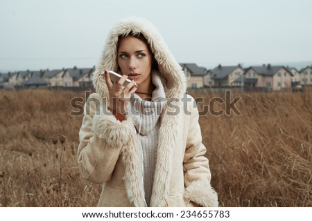 woman using smartphone in fields behind country town - stock photo