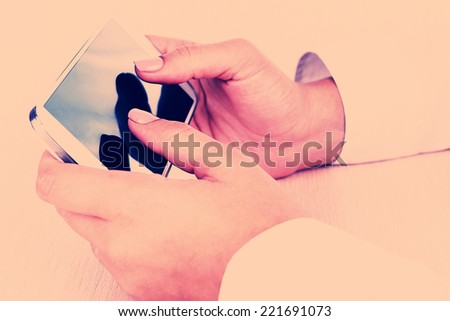 Woman using smartphone on light background - stock photo