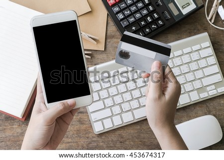 woman using smartphone to online shopping and pay by credit card, Low light, selective focus on hand, can be used for e-commerce, business, technology and internet concept, Vintage tone filter - stock photo