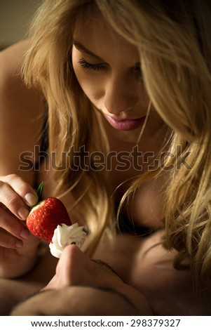 Woman using strawberry with cream during foreplay - stock photo