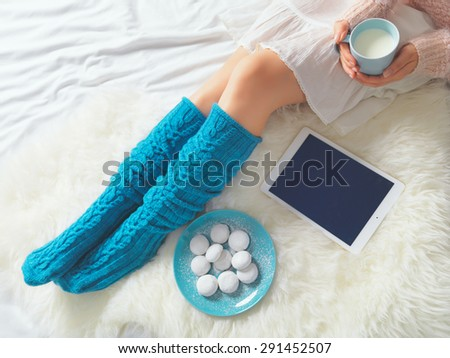 Woman using tablet at cozy home atmosphere on the bed. Young woman with cup of milk in hands enjoying free time with comfort. Soft light and comfy lifestyle concept. Technology in everyday life. - stock photo