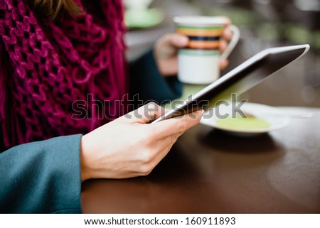 Woman using tablet computer in cafe on coffee break - stock photo