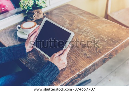 Woman using tablet in coffee shop with vintage tone. - stock photo