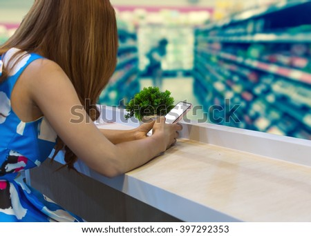 woman using the mobile phone on the seat with Abstract blurred photo of store in department store bokeh background, Shopping Online With Digital laptop, technology and internet concept - stock photo