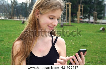 Woman using touchscreen phone outdoors in city park. Woman call by phone. - stock photo