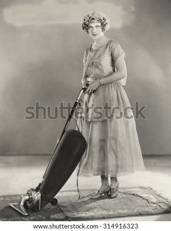 Woman vacuuming rug - stock photo