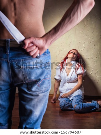 Woman victim of domestic violence and abuse. Husband holding a knife intimidates his wife - stock photo