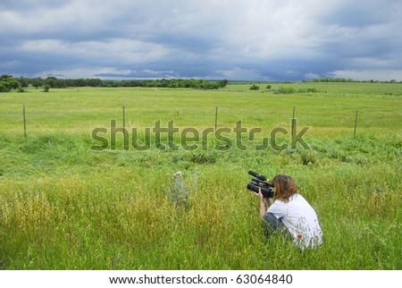 Woman videotaping an approaching storm in the grassy field of Nebraska. - stock photo