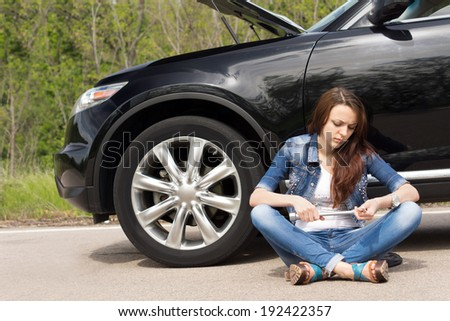 Woman waiting beside her broken down car sitting crossed legged on the road fiddling with the wheel spanner as she waits for roadside assistance - stock photo