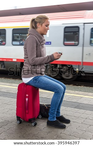 woman waiting for train and writes sms - stock photo