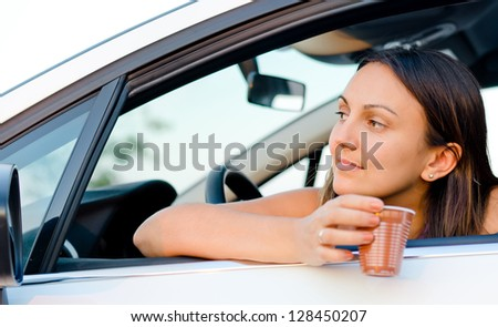 Woman waiting patiently in her car with a disposable takeaway drink in her hand looking expectantly out of the window as she waits for someone - stock photo