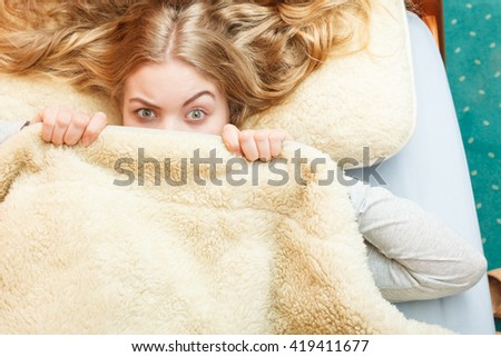 Woman waking up in bed in the morning after sleeping. Well rested young girl laying covering face with wool woolen blanket. - stock photo
