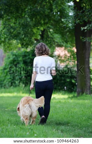 Woman walking a dog - stock photo