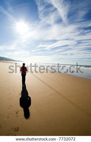 woman walking alone at the beach - stock photo