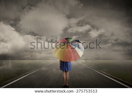 Woman walking alone with rainbow umbrella on road when rainy day - stock photo