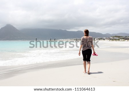 Woman walking along the Beach of Kommetjie with an upcoming storm in the background - stock photo
