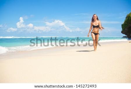 woman walking away on the idyllic beach - stock photo