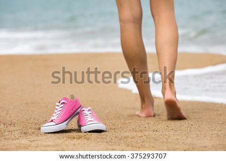 Woman walking barefoot on the beach, shoes in focus, shallow DOF - stock photo