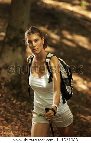 Woman walking cross country in autumn forest - stock photo