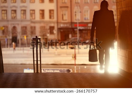 Woman walking in silhouette in Old Town, Stockholm, Sweden - stock photo