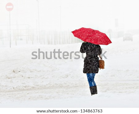 Woman walking in the winter city - stock photo