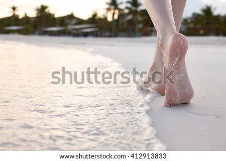 Woman walking on a beach - stock photo
