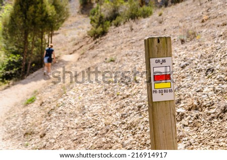 Woman walking on a footpath. Trekking in the mountain - stock photo