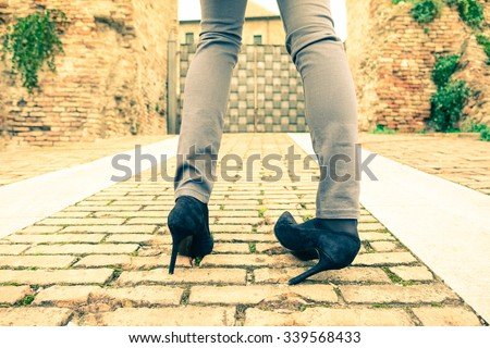 Woman walking on high heeled shoes - Closeup of young girl legs with twisted ankle - Slim teenager wearing trendy tight jeans pants - Concept of youth fashion and social problems related to anorexia - stock photo