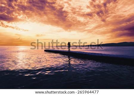Woman walking on pier near the sea at sunset, tranquil scene. Beautiful seascape - stock photo