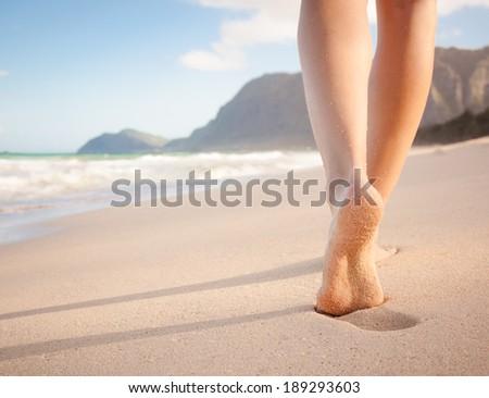 Woman walking on sand beach leaving footprints in the sand. Closeup of female feet at the beach in Hawaii. Beach travel.  - stock photo