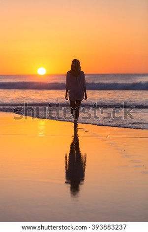 Woman walking on sandy beach in sunset leaving footprints in the sand. Beach, travel, concept. Copy space. Vertical composition. - stock photo
