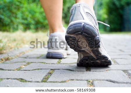 Woman walking on sidewalk, sport shoes closeup - stock photo