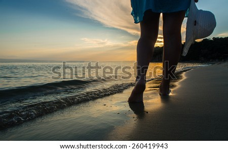 Woman walking on the beach at sunset - stock photo