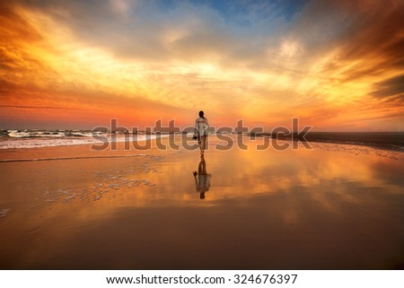 woman walking on the beach near the ocean at the sunset - stock photo