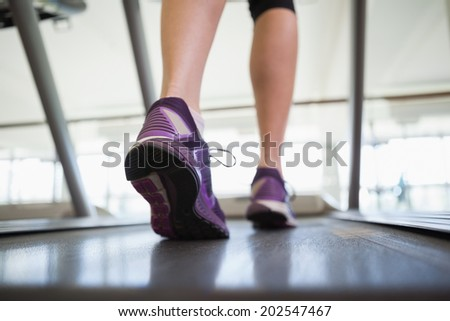 Woman walking on the treadmill at the gym - stock photo