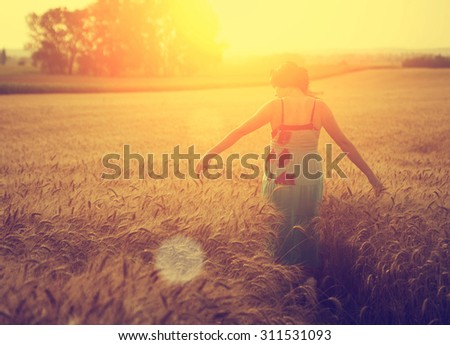 Woman walking on wheat field in sunset - stock photo
