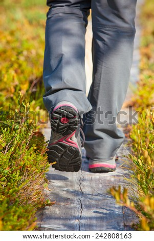 Woman walking on wooden path at swamp in Finland. Shoes close-up view. - stock photo
